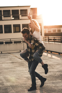 Happy young man giving his  girlfriend a piggyback ride on roof terrace at sunset - UUF12363