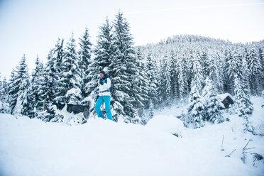 Austria, Altenmarkt-Zauchensee, young woman with dog in winter forest - HHF05526