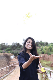 Thailand, Chiang Mai, happy young woman throwing flowers up in the sky surrounded by nature - IGGF00196