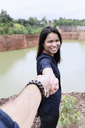 Thailand, Chiang Mai, happy young woman holding hand of her partner at grand canyon - IGGF00199