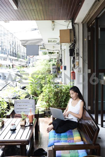 Woman using laptop sitting on terrace bench - IGGF00212