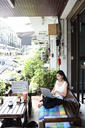 Woman using laptop sitting on terrace bench - IGGF00212