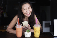 Portrait of happy woman with cell phone and smoothies - IGGF00215