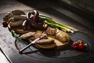 Liver sausage, blood sausage,  spring onion, red radish, chives, mustard, bread on chopping board, hotplate - MAEF12459