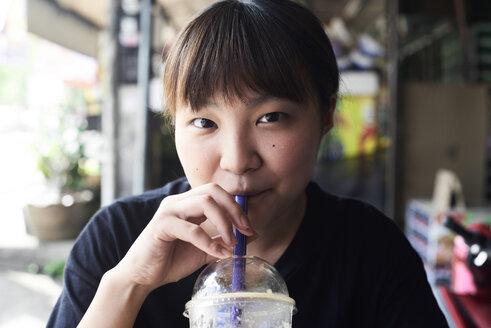 Portrait of woman drinking smoothie - IGGF00217