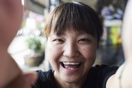 Portrait of laughing woman taking selfie with smartphone - IGGF00223