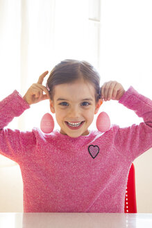 Portrait of laughing girl with pink Easter eggs - LVF06434