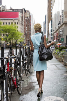 USA, New York, young blonde african-american woman with smart phone walking on walkway - MAUF01237