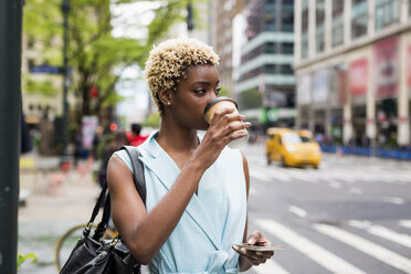 USA, New York, young blonde african-american woman with coffee mug and smart phone - MAUF01240