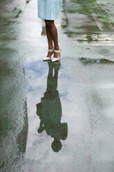 USA, New York, young african-american woman standing on street, high heels, water reflection in puddle - MAUF01243