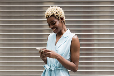 USA, New York, young blonde african-american woman using smartphone, smiling - MAUF01249