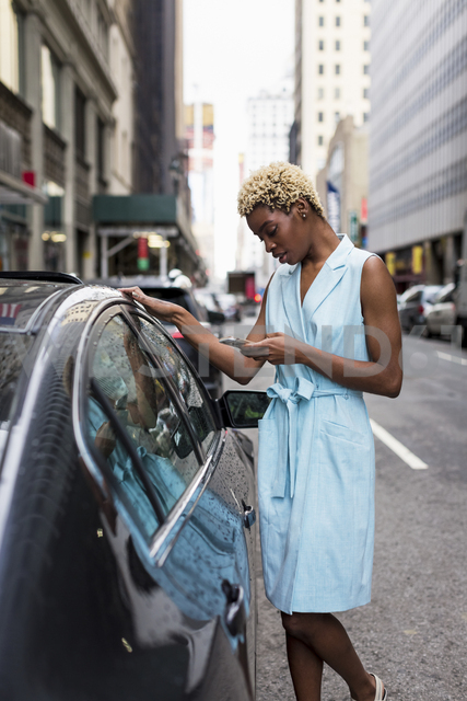 USA, New York, young blonde african-american woman using smartphone - MAUF01252 - Mauro Grigollo/Westend61