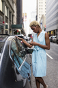 USA, New York, young blonde african-american woman using smartphone - MAUF01252