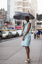 USA, New York, young blonde african-american woman with umbrella - MAUF01255