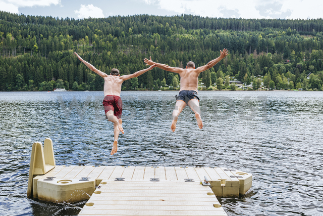 Germany, Lake Titisee, two men jumping into lake from a jetty - KIJF01717
