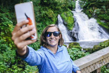Germany, Triberg, woman taking a selfie with mobile phone in front of Triberg Waterfalls - KIJF01720