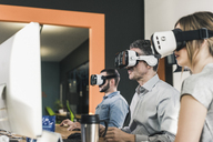 Colleagues wearing VR glasses in office - UUF12414
