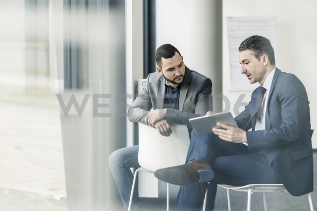 Two businessmen with tablet talking in office at the window - UUF12420 - Uwe Umstätter/Westend61