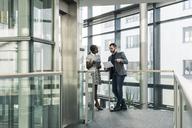 Businessman and businesswoman talking on office floor - UUF12435