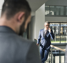 Businessman talking on cell phone on office floor - UUF12438