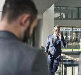 Businessman talking on cell phone on office floor - UUF12438