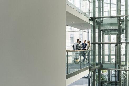 Business people talking on office floor - UUF12441