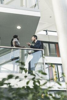 Businessman and woman talking on office floor - UUF12444