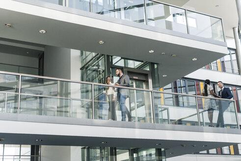Business people talking on office floor - UUF12447
