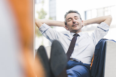 Portrait of businessman relaxing in lounge - UUF12453