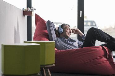 Smiling businessman sitting in beanbag wearing headphones - UUF12465
