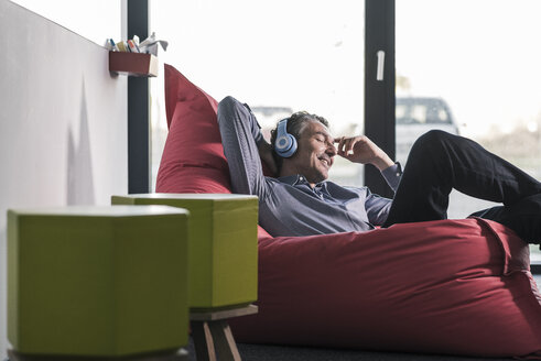 Smiling businessman sitting in beanbag wearing headphones - UUF12465