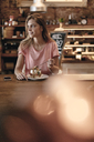 Young woman sitting cafe, eating granola for breakfast - GUSF00180