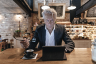 Senior businessman sitting in cafe, using digital tablet, reading - GUSF00183