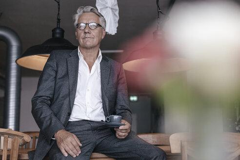Senior businessman drinking coffee, sitting on table - GUSF00186