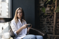 Young woman sitting in cafe, drinking coffee - GUSF00195