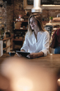 Laughing blond woman sitting in cafe, using tablet - GUSF00201