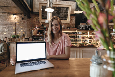 Young woman sitting in cafe, with laptop on table - GUSF00213