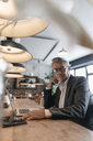Senior businessman sitting in cafe working on laptop - GUSF00237