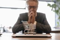 Senior businessman looking at shopping cart on laptop - GUSF00240