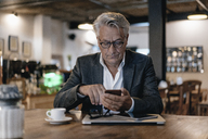 Senior businessman sitting in cafe, checking messages on smartphone - GUSF00252