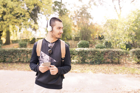 Young man with headphones and cell phone outdoors - FMOF00326