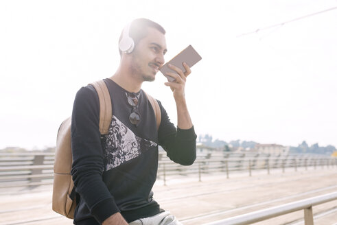 Young man with headphones and cell phone at tram stop outdoors - FMOF00329