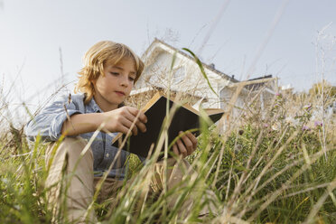Portrait of a boy sitting on a meadow reading a book - KMKF00066