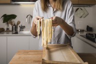 Woman preparing homemade pasta, holding row noodles, pasta harp - MAUF01262