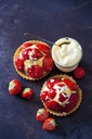 Two strawberry tartlets with custard and white chocolate shaving on dark ground - CSF28581