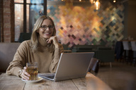 Portrait of laughing businesswoman with laptop in a restaurant - SUF00341