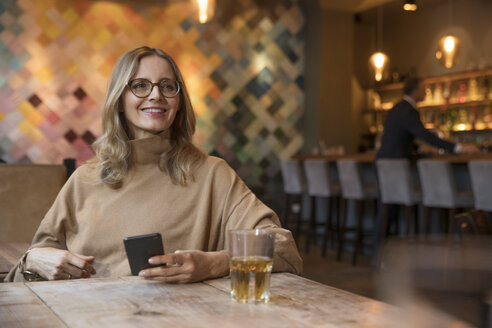 Portrait of smiling businesswoman in a restaurant - SUF00344