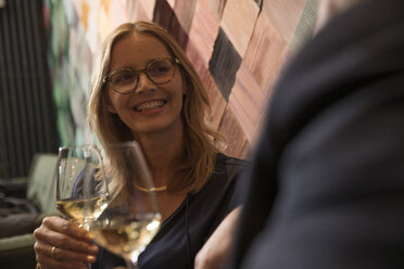 Portrait of laughing woman drinking wine in bar - SUF00371