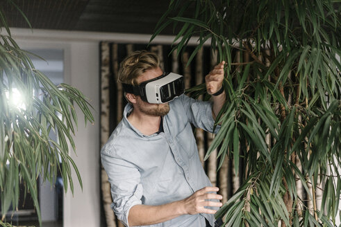 Man wearing VR glasses surrounded by plants - JOSF02019