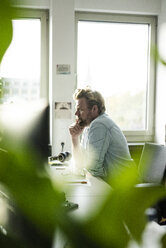 Businessman sitting at desk in office thinking - JOSF02028